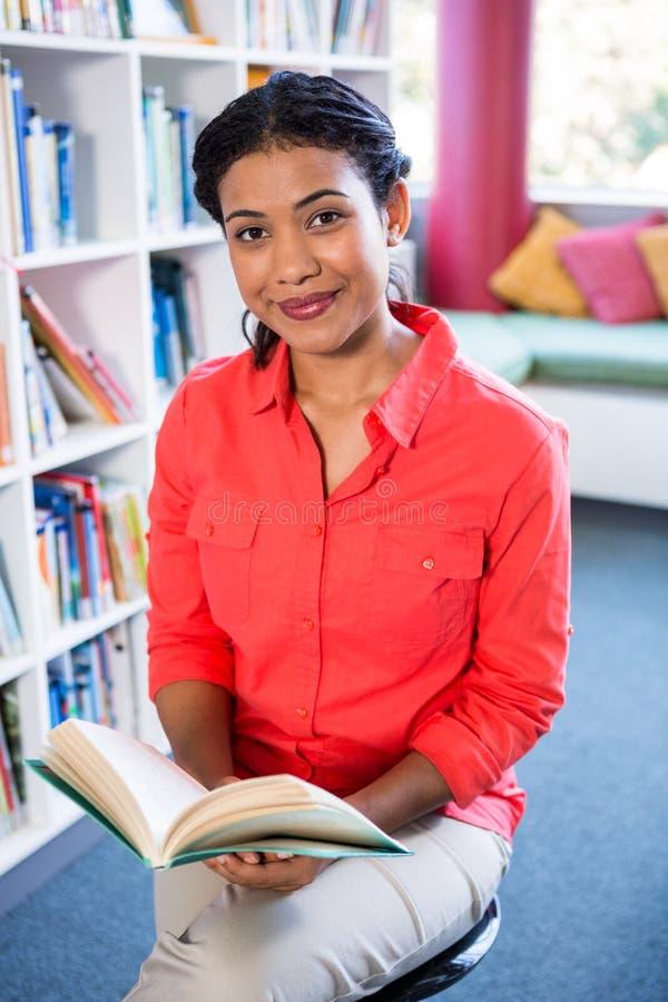 Porträt des Lehrerlesebuches an der Bibliothek in der Schule lizenzfreies stockfoto