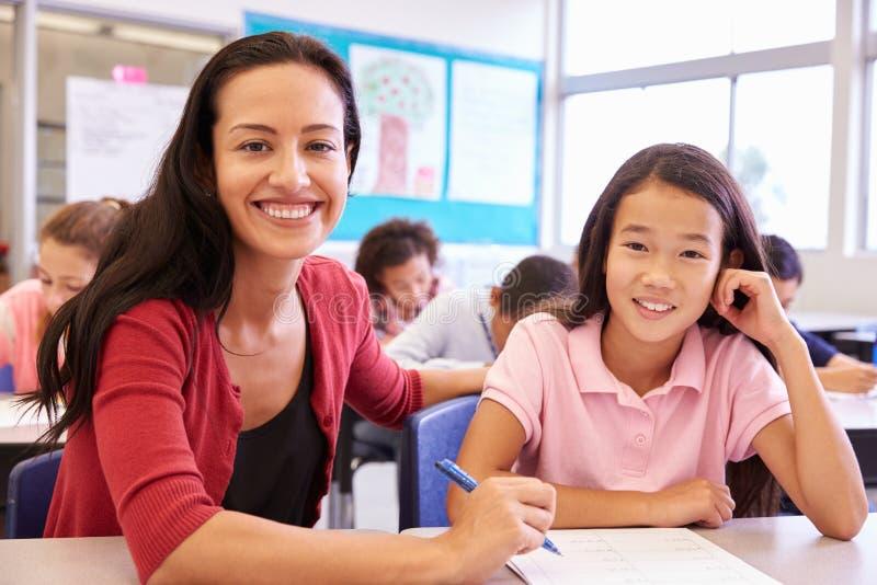 Porträt des Lehrers mit Volksschulemädchen an ihrem Schreibtisch lizenzfreie stockfotos