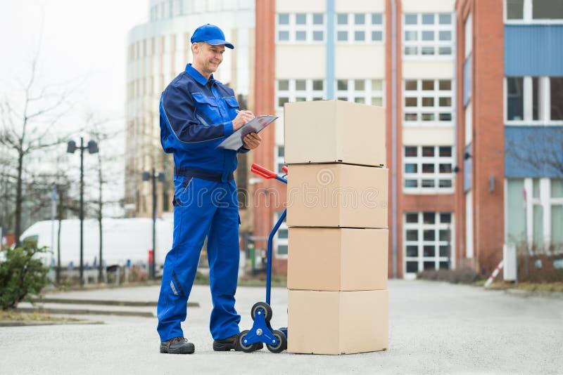 Porträt des Lieferers mit Paketen und Klemmbrett stockfoto