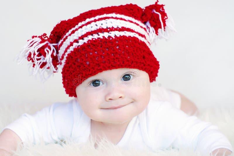 Porträt des lustigen Babys in der roten Strickmütze lizenzfreies stockfoto