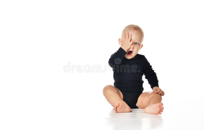 Porträt des lustigen gähnenden Jungen, der auf dem Boden lokalisiert auf Weiß sitzt lizenzfreie stockfotos