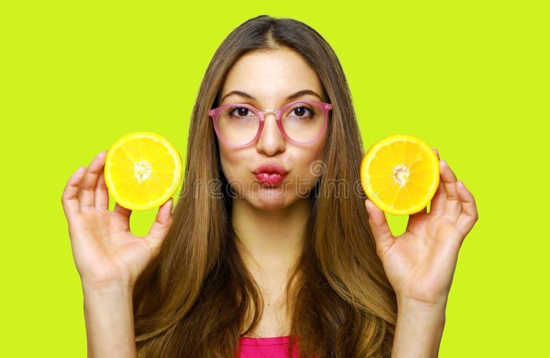 Porträt des lustigen glücklichen Mädchens, das Hälften der Orange nahe Gesicht hält stockfotografie
