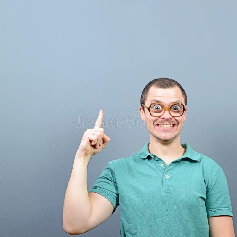 Porträt des lustigen Sonderlings mit den großen Augen, die eine Idee haben und am leeren Raum oben gegen grauen Hintergrund darst lizenzfreies stockbild