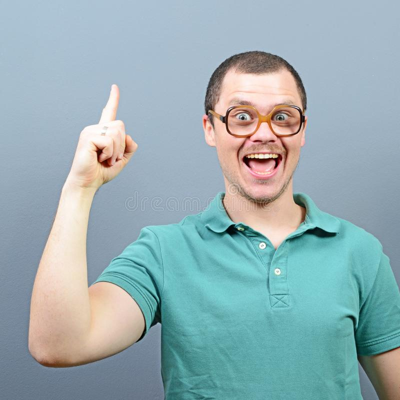 Porträt des lustigen Sonderlingskerls, der eine Idee gegen grauen Hintergrund hat lizenzfreie stockbilder