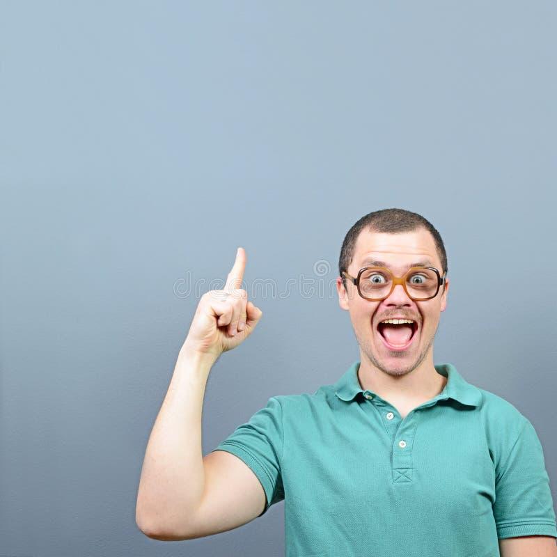 Porträt des lustigen Sonderlingskerls, der eine Idee hat und am leeren Raum oben gegen grauen Hintergrund darstellt lizenzfreies stockfoto