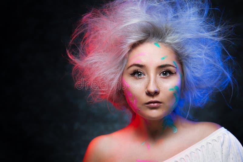 Porträt des Mädchenmalers mit Farbfarbe auf Gesicht mit Tätowierung an Hand lizenzfreie stockfotos