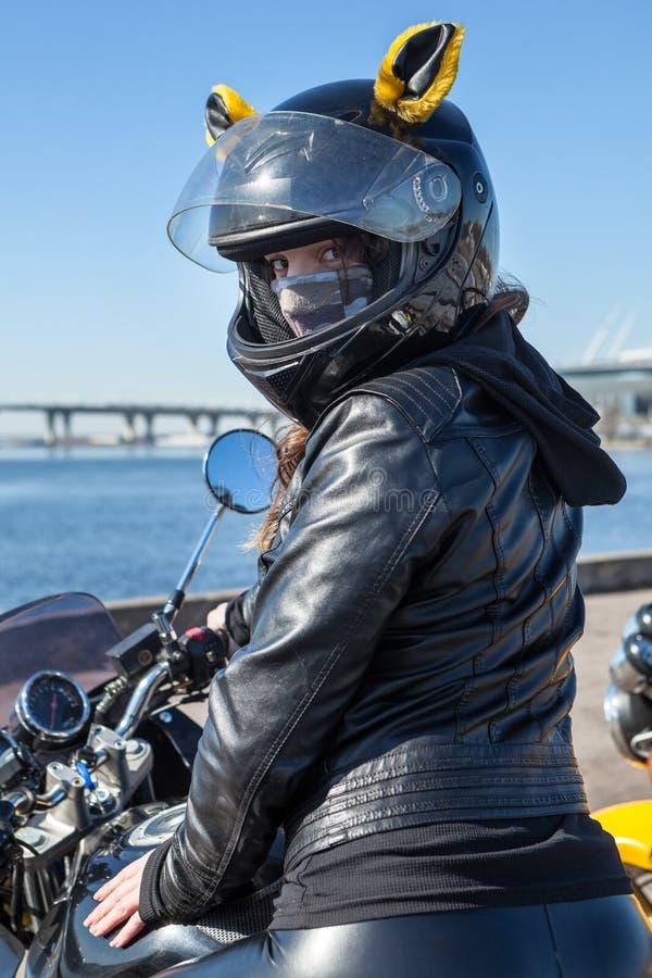 Porträt des Mädchenmotorradreiters, der rückwärts, sitzend auf einem Fahrrad im schwarzen Sturzhelm mit den gelben Ohren schaut stockfoto