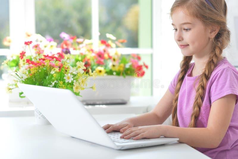 Portr?t des M?dchens, das bei Tisch modernen Laptop verwendet stockbilder