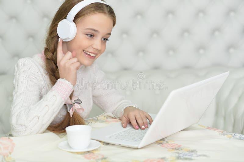 Porträt des Mädchens in den Kopfhörern unter Verwendung des Laptops stockbild