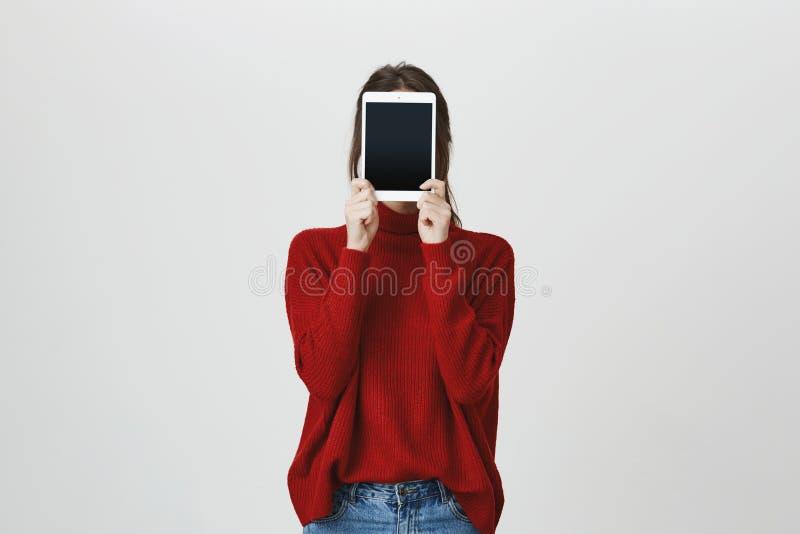 Porträt des Mädchens in der modischen roten Strickjacke, die ihr Gesicht mit einer Tablette steht nahe weißer Wand bedeckt Techno lizenzfreies stockfoto