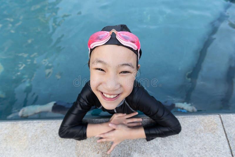 Porträt des Mädchens entspannend im Swimmingpool, kleines Mädchen im Badeanzug das Wasser genießend stockbild
