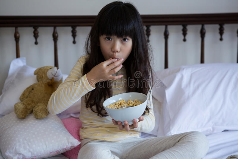 Porträt des Mädchens Frühstück auf Bett essend stockbild