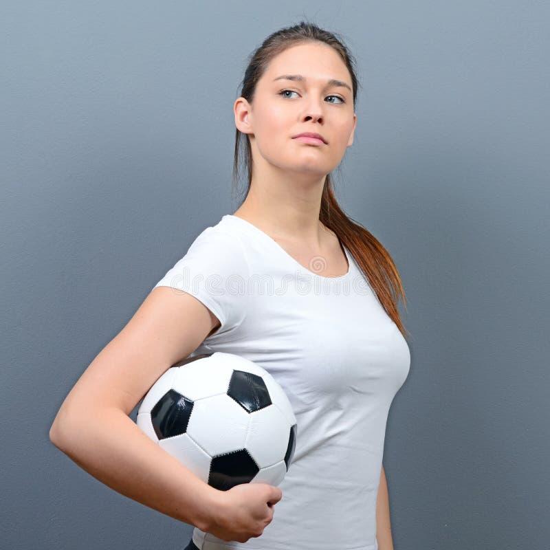 Porträt des Mädchens Fußball gegen grauen Hintergrund halten lizenzfreies stockbild