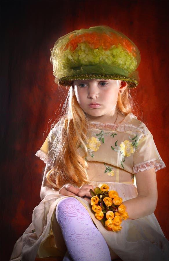 Porträt des Mädchens im Hut mit Blumenstrauß von Blumen lizenzfreie stockbilder