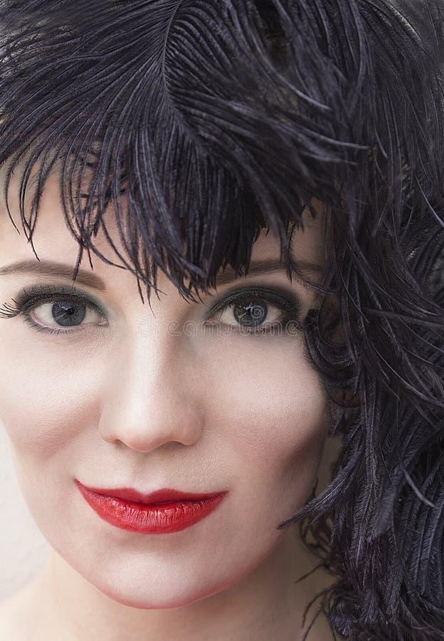 Porträt des Mädchens im schwarzen Federkopfschmuck Rauchiges Augenmake-up lizenzfreies stockbild