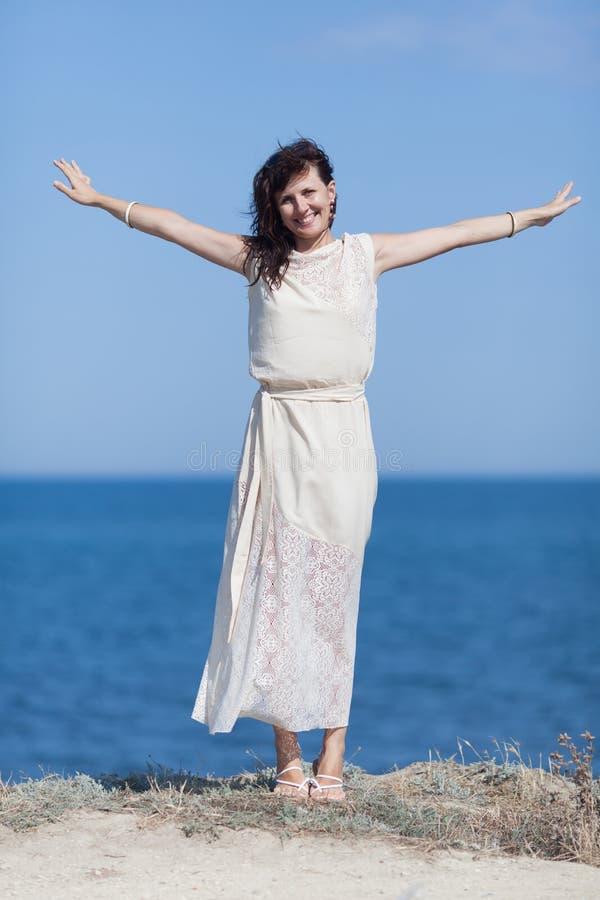 Porträt des Mädchens im weißen ärmellosen Kleid mit Arme outstretche lizenzfreies stockfoto