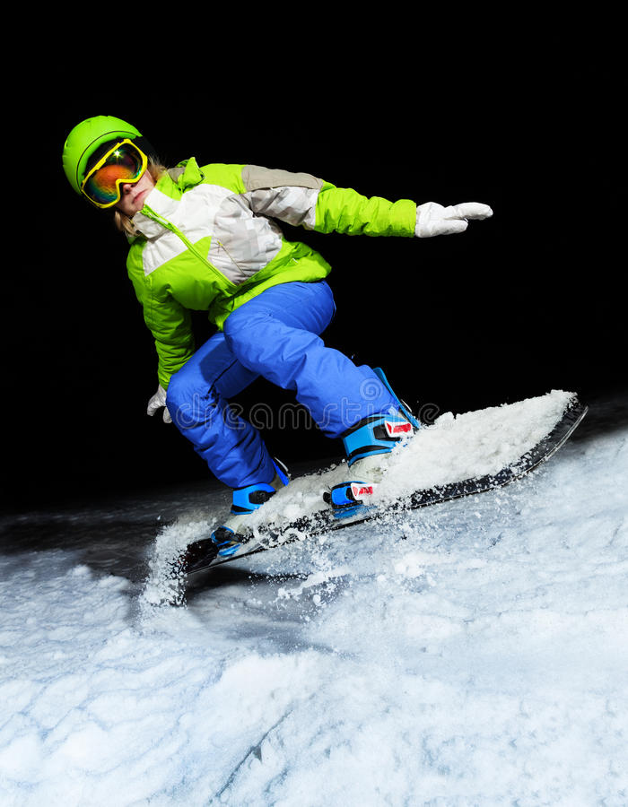 Porträt des Mädchens springend auf Snowboard nachts lizenzfreies stockbild