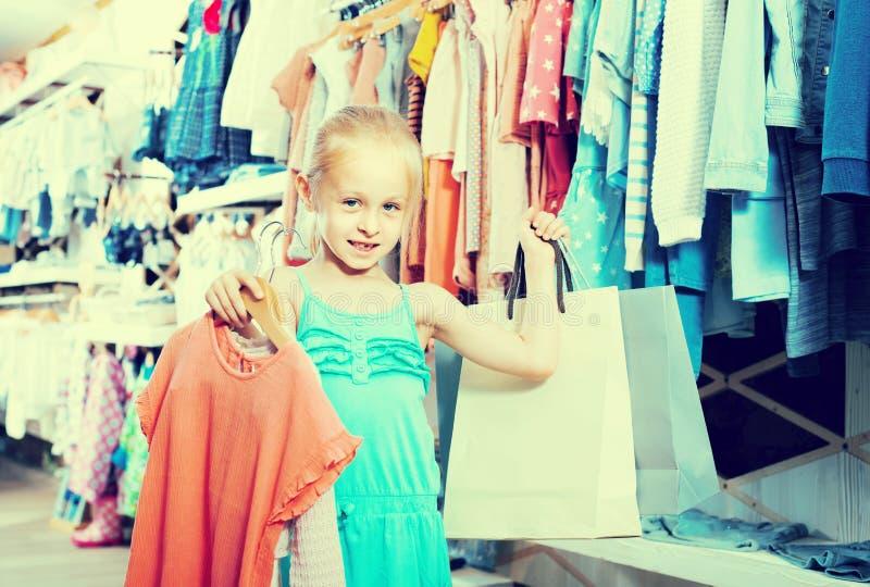Porträt des Mädchens stehend im Kinderkleidungsspeicher mit Einkaufsb stockfotografie