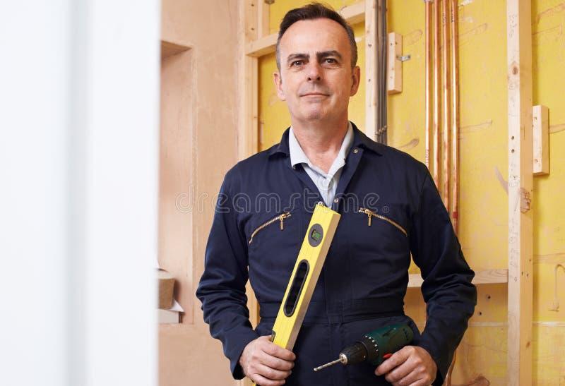 Porträt des männlichen Erbauers With Spirit Level und der elektrischen Bohrmaschine stockbilder