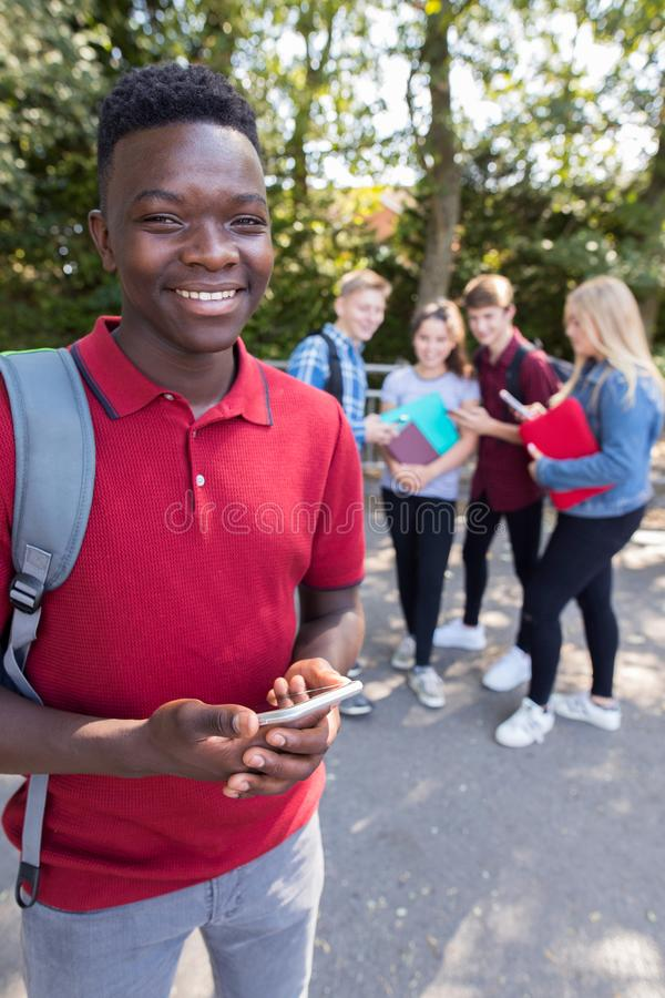 Porträt des männlichen jugendlichen hohen Schülers Outdoors With Frien stockbild