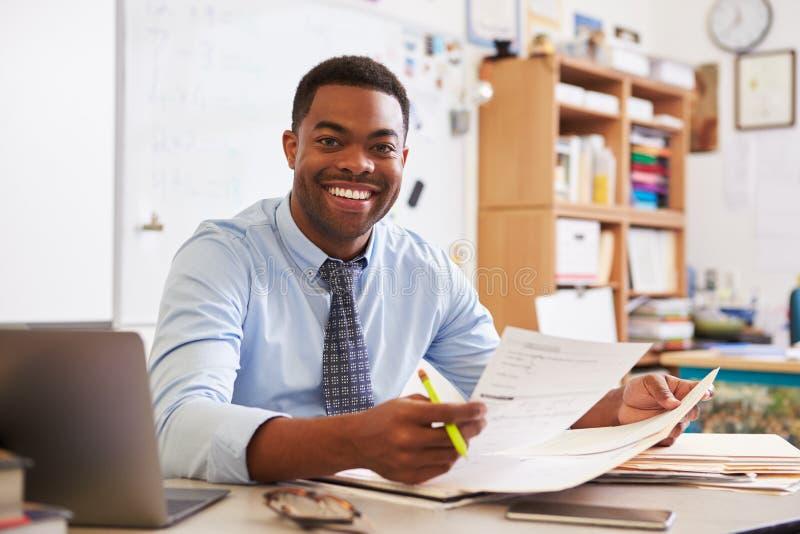 Porträt des männlichen Lehrers des Afroamerikaners, der am Schreibtisch arbeitet lizenzfreies stockbild
