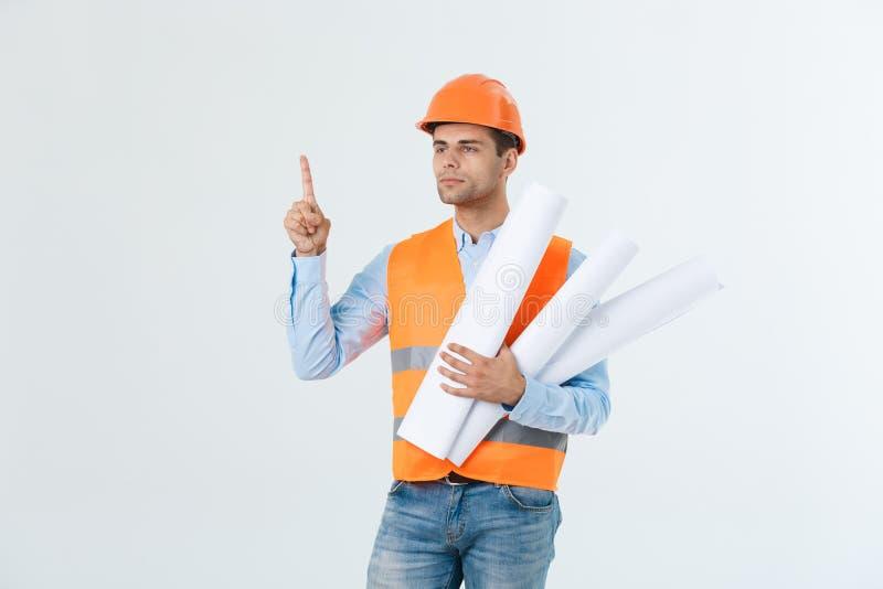 Porträt des männlichen Standortauftragnehmeringenieurs mit dem Schutzhelm, der Blaupausenpapier hält Lokalisiert über weißem Hint lizenzfreies stockfoto