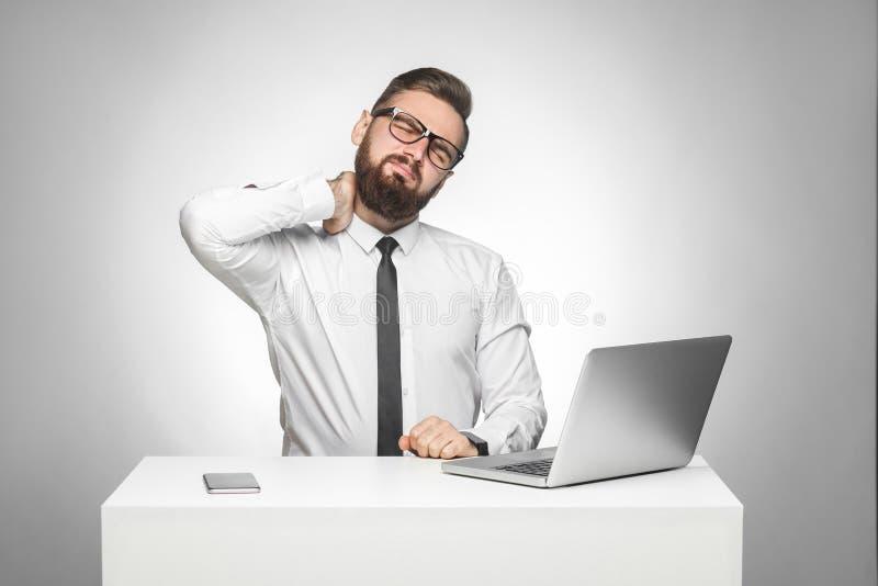 Porträt des müden jungen Chefs des unhealphy Umkippens im weißen Hemd und Abendgarderobe sitzen im Büro und haben die starken Sch stockbild