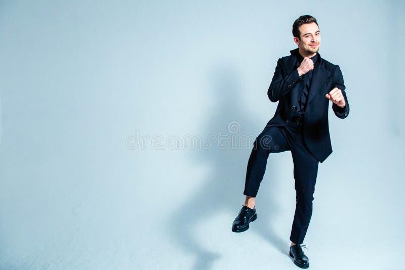 Porträt des Mannes in einem schwarzen Anzug in einer kämpfenden Position, Händchenhalten nahe seinem Kasten, lächelnd und schauen lizenzfreie stockfotografie