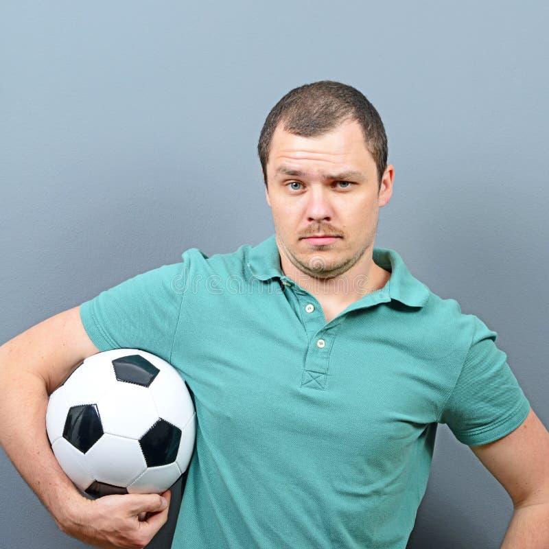 Porträt des Mannes Fußball halten - Fußballfananhänger- oder -spielerkonzept lizenzfreies stockbild