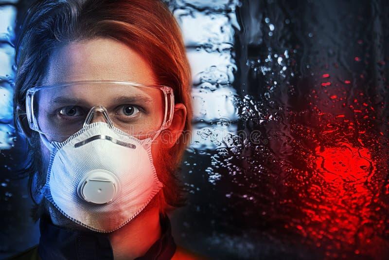 Porträt des Mannes im Respirator über regnerischem Fenster lizenzfreie stockbilder