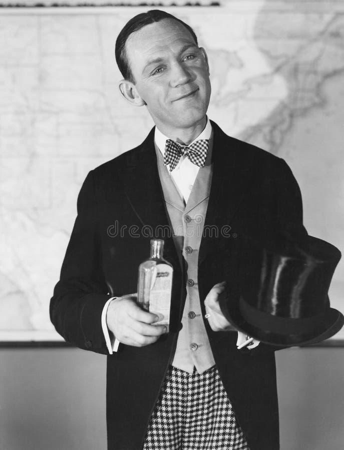 Porträt des Mannes mit Zylinder und Flasche stockbild