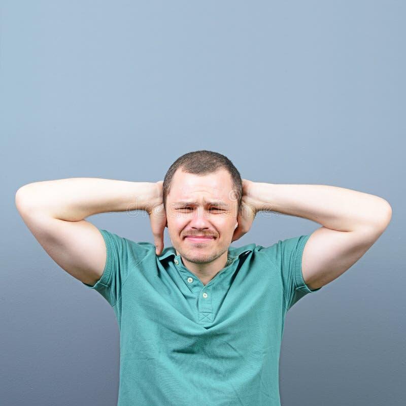 Porträt des Mannes Ohren mit den Händen gegen grauen Hintergrund bedeckend stockfotografie