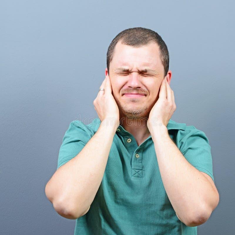 Porträt des Mannes Ohren mit den Händen gegen grauen Hintergrund bedeckend lizenzfreie stockbilder