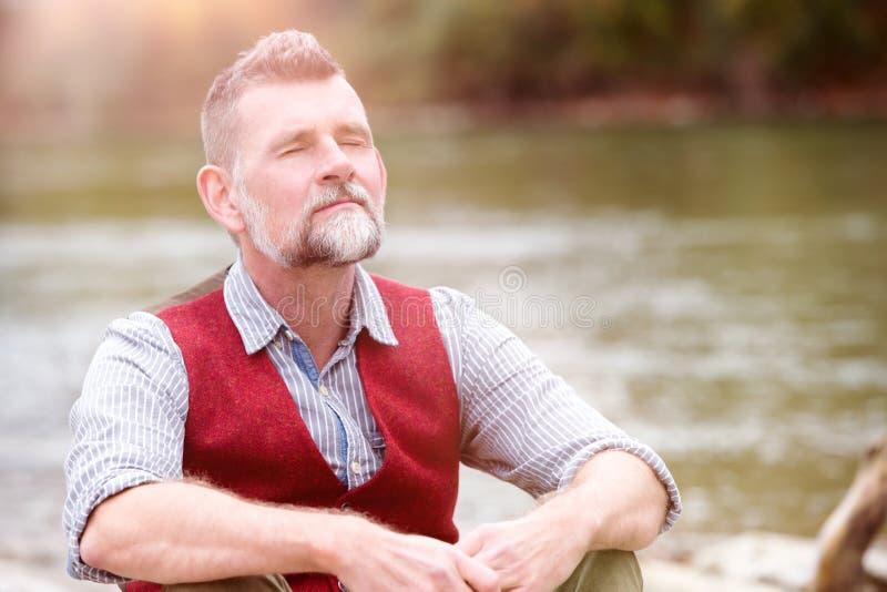 Porträt des Mannes in seinem 50s, das durch den Fluss sitzt lizenzfreie stockfotos