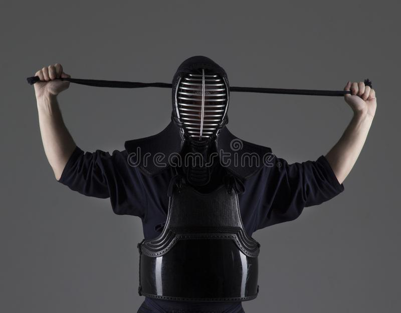 Porträt des Mannes in Tradition kendo Rüstung, die seinen Sturzhelm setzt und für den Kampf sich vorbereitet lizenzfreies stockbild