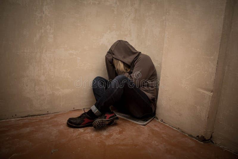 Porträt des Mannes traurig, Drogenabhängigemann, der auf dem Boden in der Ecke sitzt stockfotos