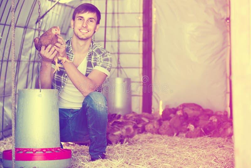 Porträt des Mannlandwirts mit Huhn auf Geflügelfarm zuhause lizenzfreie stockfotos