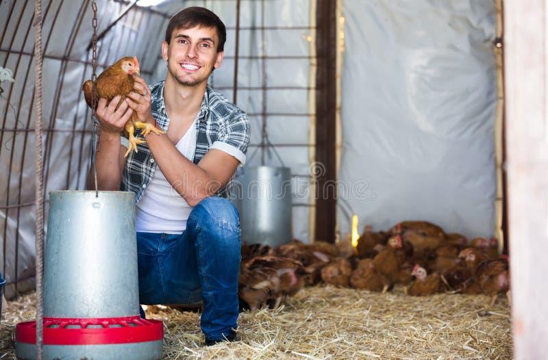 Porträt des Mannlandwirts mit Huhn auf Geflügelfarm zuhause lizenzfreie stockfotografie