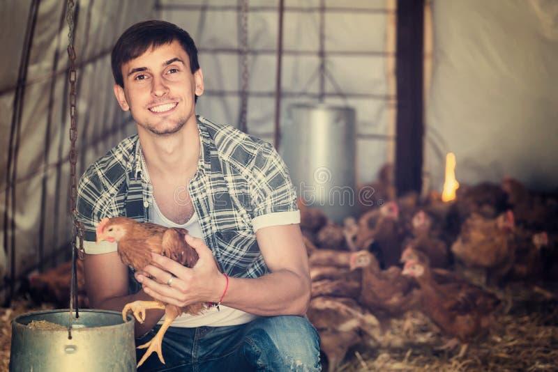 Porträt des Mannlandwirts mit Huhn auf Geflügelfarm zuhause stockbilder