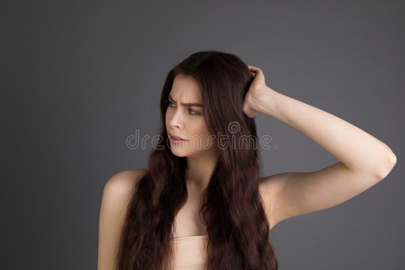 Porträt des missfallenen jungen brunette Mädchens, das Haar berührt stockfoto