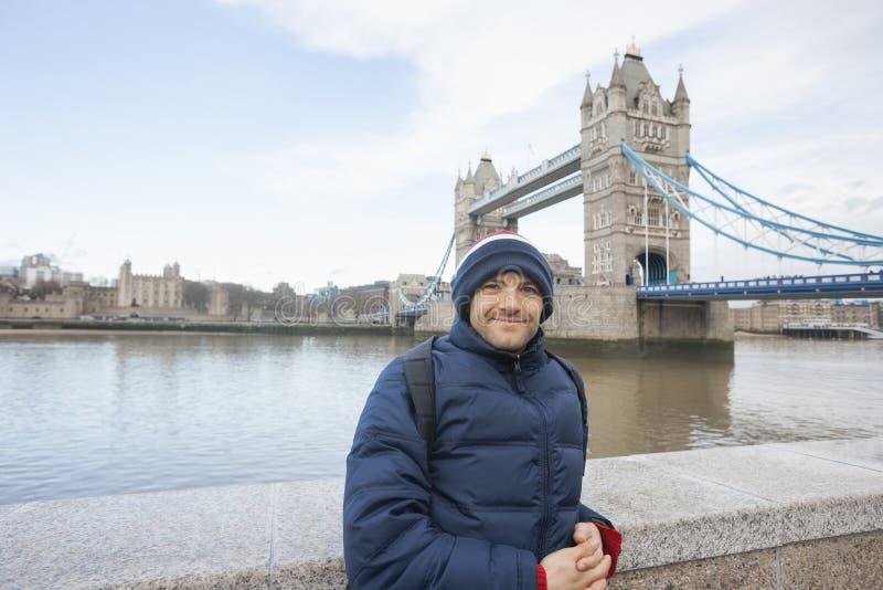 Porträt des mittleren erwachsenen Mannes in der warmen Kleidung, die vor Turmbrücke, London, Großbritannien steht stockbild