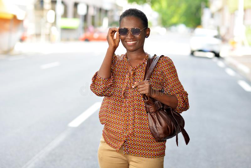 Porträt des modernen modischen Mädchens mit Handtasche in der Hand stockfotografie