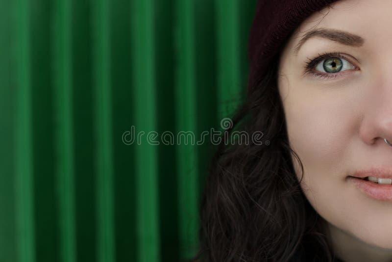 Porträt des modischen Hippie-Mädchens, das am grünen Wand-Hintergrund steht St?dtisches Mode-Konzept Kopieren Sie Platz lizenzfreie stockfotografie