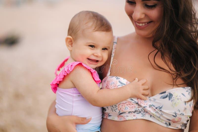 Porträt des Muttergriffbabys auf Händen auf dem Strand im Meer Mutter und Tochter im Badeanzug Schlie?en Sie oben von sch?nem stockbilder