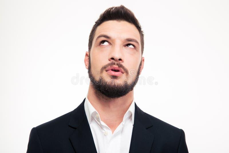 Porträt des nachdenklichen attraktiven jungen Mannes, der oben denkt und schaut lizenzfreie stockfotografie