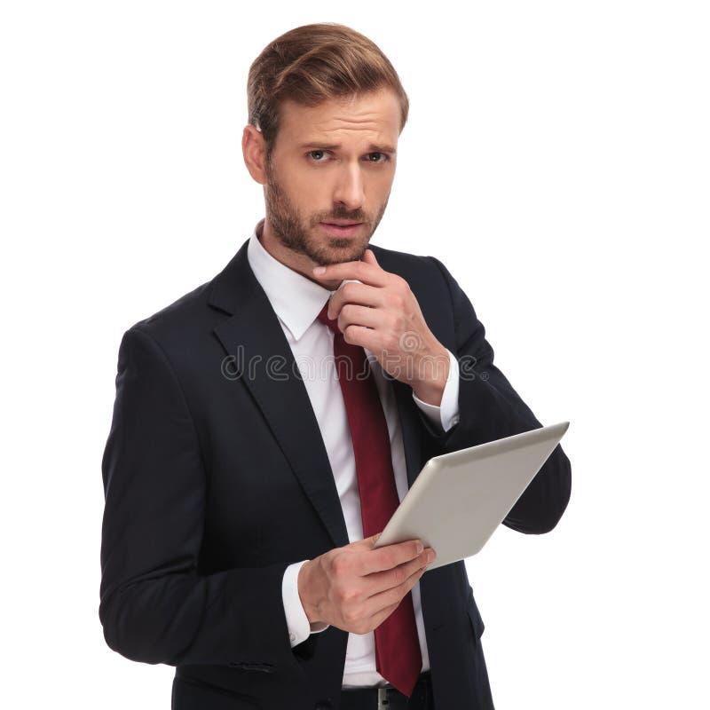 Porträt des nachdenklichen jungen Geschäftsmannes, der seine Auflage hält stockfoto