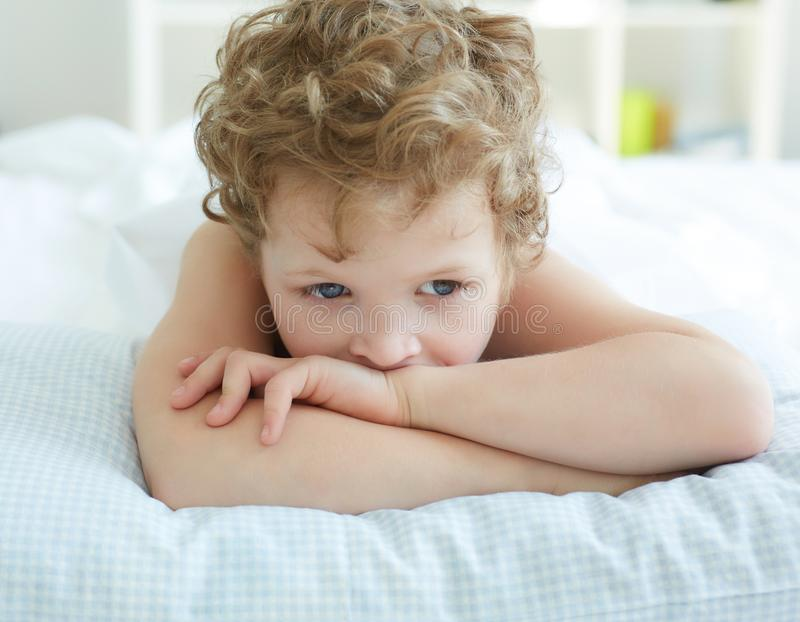 Porträt des nachdenklichen kleinen Jungen, der auf Bett liegt stockfotos