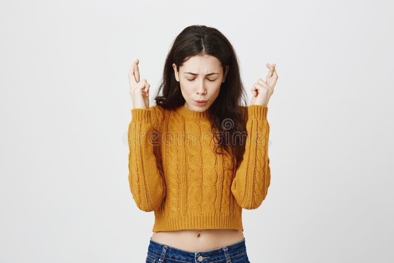 Porträt des nervösen jungen europäischen Mädchens mit besorgtem Ausdruck, Hände mit den gekreuzten Fingern beim Bitten anhebend o stockfotos