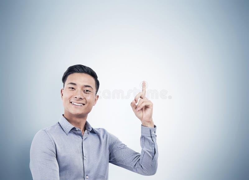 Porträt des netten asiatischen Geschäftsmannes, der oben zeigt stockfotografie