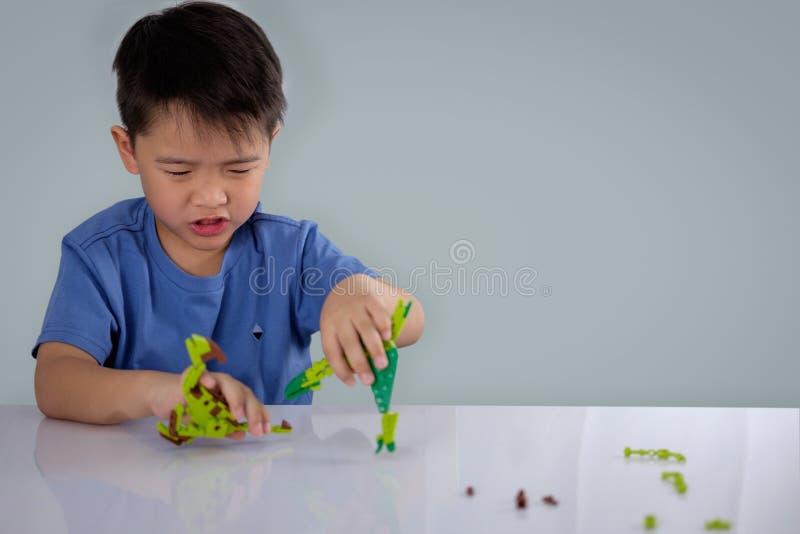 Porträt des netten asiatischen Jungen, der mit bunten Plastikspielzeugziegelsteinen spielt lizenzfreies stockfoto